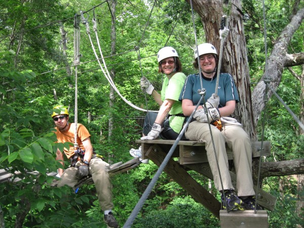 Atlanta writer Hope Philbrick (left) and Julia Bayly take a tree-top break from zip lining and cable bridges with their guide at Historic Banning Mills in Georgia.
