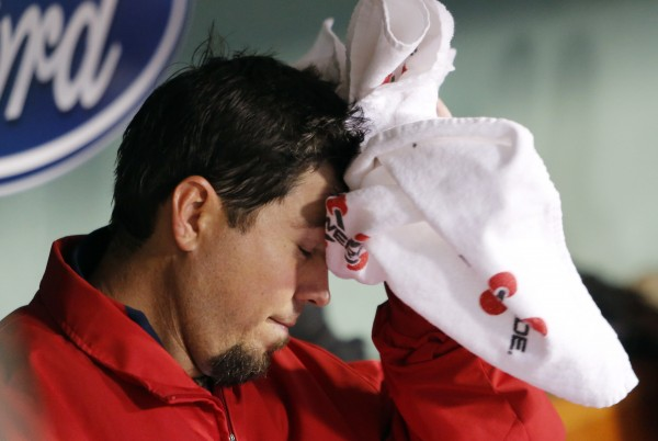 Boston Red Sox starting pitcher Josh Beckett wipes his head in the dugout after being taken out in the third inning of a baseball game against the Cleveland Indians in Boston, Thursday, May 10, 2012.