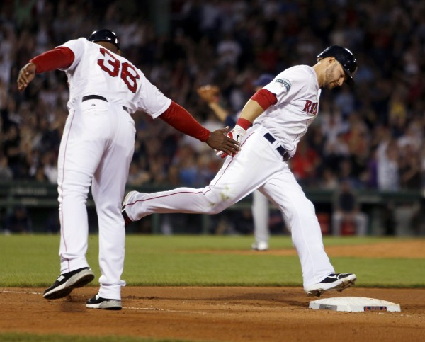 Boston Red Sox first base coach Alex Ochoa (36) reaches out to Cody Ross as Ross rounds the bases on a solo home run in the sixth inning of a baseball game against the Cleveland Indians in Boston, Saturday, May 12, 2012. (AP Photo/Michael Dwyer)