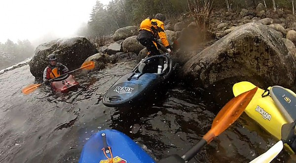Dr. Adam Lauer (center) drags his kayak up onto the rocks as he was getting ready for a portage to run Upper Gordon Falls on the Mattawamkeag River on April 8th 2012.  On the left is Travis Boudreau. BDN photo by Gabor Degre
