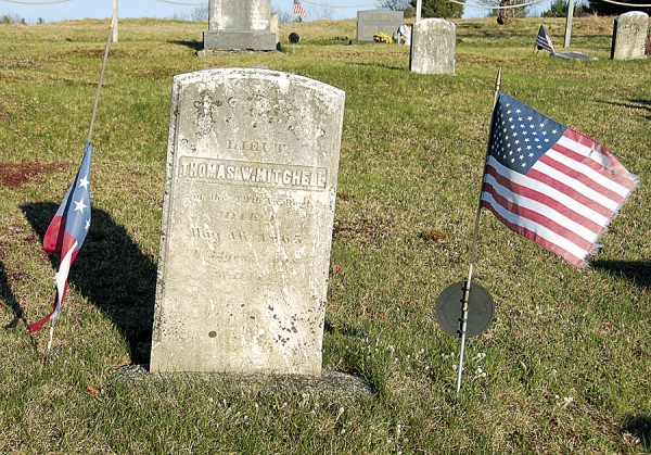 American and Confederate national flags honor the headstone of Lt. Thomas W. Mitchell, a Confederate soldier who loved and married a Dedham woman, Mary Ester Dexter. Captured in late May 1864, Mitchell was released from prison in mid-May 1865 and shipped to Maine. He probably envisioned a happy reunion with Mary and their daughter, Anna, who had lived in Dedham since Mitchell sent them there from Virginia in 1861. Afflicted by congested lungs, Mitchell died in Bangor on May 16, 1865. Mary buried him at Central Cemetery in Dedham.