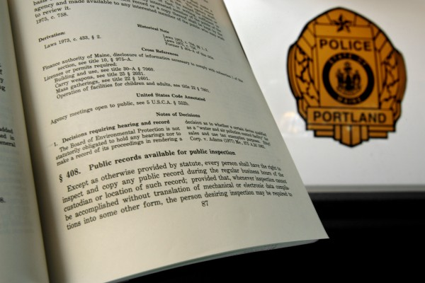 The Maine Freedom of Access Law is seen in a copy of the Maine Revised Statutes Annotated, Friday, June 30, 2006, by a Portland Police Department vehicle in Portland, Maine.