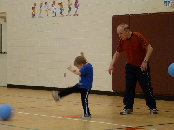 Physical education teacher Gary Spinney instructs kindergartener Coben Seavey-Bickford, 5, to kick a ball and then run to first base during gym class at Camden-Rockport Elementary School on April 12, 2012.
