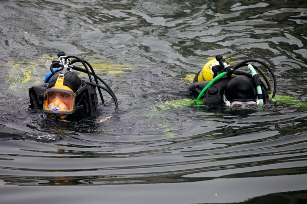 Divers search for Nathan Bihlmaier between wharves on the Portland waterfront early Monday evening. Bihlmaier went missing early Sunday morning.