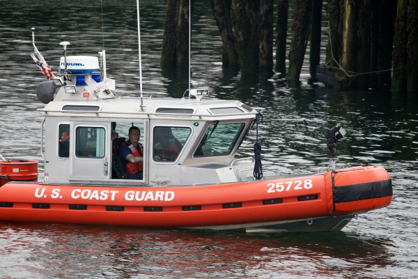 A U.S. Coast Guard boat joins the search for Nathan Bihlmaier between wharves on the Portland waterfront early Monday evening. Bihlmaier went missing early Sunday morning.