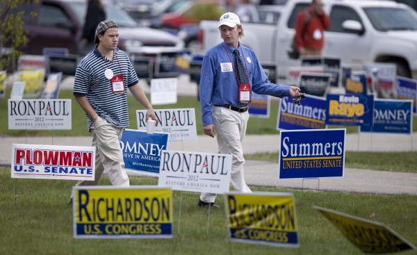 Cumberland County delegates Daniel Bassett (left) and Kyle Dixon walk by candidates' signs at the Maine Republican Convention at the Augusta Civic Center in Augusta on Sunday, May 6, 2012.