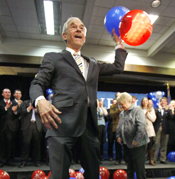 In this Feb. 11, 2012 file photo, Republican presidential candidate Rep. Ron Paul, R-Texas, throws balloons from the stage after speaking to supporters in Portland, Maine, following his loss in the Maine caucus.
