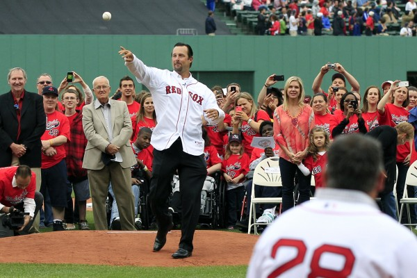 Newly retired Boston Red Sox pitcher Tim Wakefield throws a ceremonial first pitch to former Red Sox catcher Doug Mirabelli during a ceremony to honor Wakefield's career prior to a baseball game against the Seattle Mariners at Fenway Park in Boston, Tuesday, May 15, 2012.