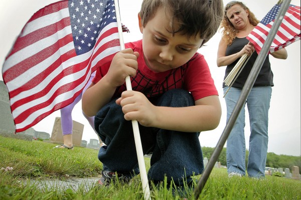 Victoria Ponte (right) watches her son Harrison Corrie, 4, place an American flag at the grave of a veteran at Sacred Heart cemetery in the north end of New Bedford, Mass., Friday, May 25, 2012, in advance of Monday's Memorial Day observance.