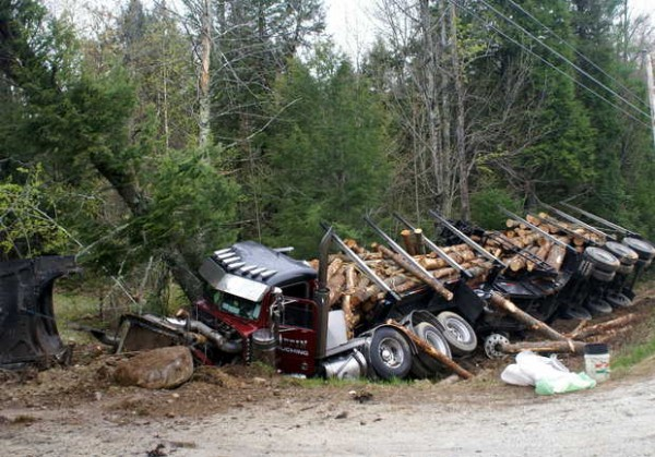 A logging truck owned by Coffin Trucking lies in a ditch on Route 117 in Harrison after a head-on collision with a red convertible.