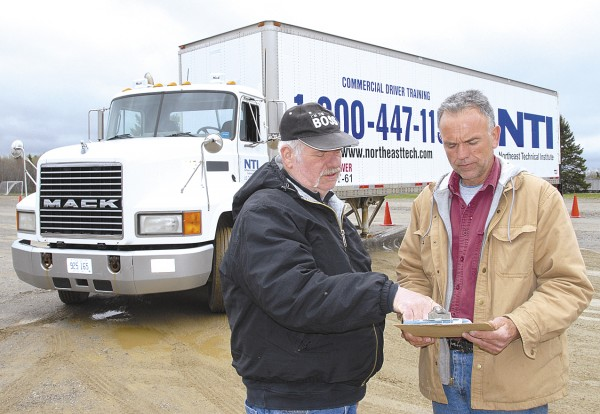 At the Northeast Technical Institute's driver training facility in Hampden, CDL instructor Bob Daigle (left) discusses a pre-trip inspection with Barry Wood of Old Town. Wood is enrolled in the CDL program at NTI.