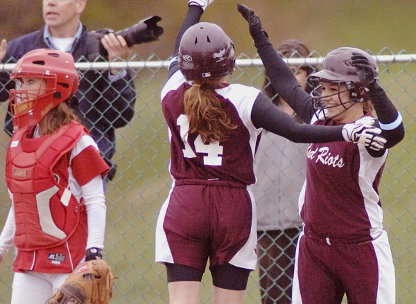 Orono softball players Leyah Bryant (14) and Caleigh Paul (right) celebrate after scoring the tying and go-ahead runs in the seventh inning of their game against Dexter in Dexter on Wednesday, May 2, 2012.