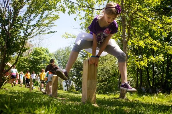 Taja Wilkins, 9, a fourth-grader at the Ocean Avenue School in Portland, leapfrogs over a post in a new fitness course at the school Monday, May 21, 2012.