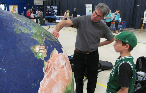 Stuart Rose of the Maine Department of Environmental Protection shows Spencer Strong, a fifth-grader from Hebron Station School, his model globe standing more than 5 feet tall at the Southern Maine Children's Water Festival in Portland on Friday, May 18, 2012. The carbon fiber Earth, which Rose constructed, features blinking lights where environmental disasters have occurred.