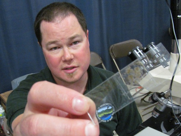 Fred Gallant of the Maine Department of Environmental Protection's Bureau of Water Quality eyes a microscope slide of sludge harvested from Kennebunkport's wastewater treatment facility Friday, May 18, 2012, at the Southern Maine Children's Water Festival in Portland. Gallant displayed microorganisms found in the sewage on a television screen for students at the festival to see.