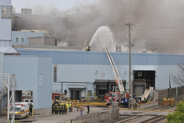 Firefighters and emergency personnel gather as they fight a fire following an explosion Monday, May 28, 2012 at the Verso Paper Co. plant in Sartell, Minn. One person was killed and at least four others were injured in the explosion that caused a large fire at the paper mill.