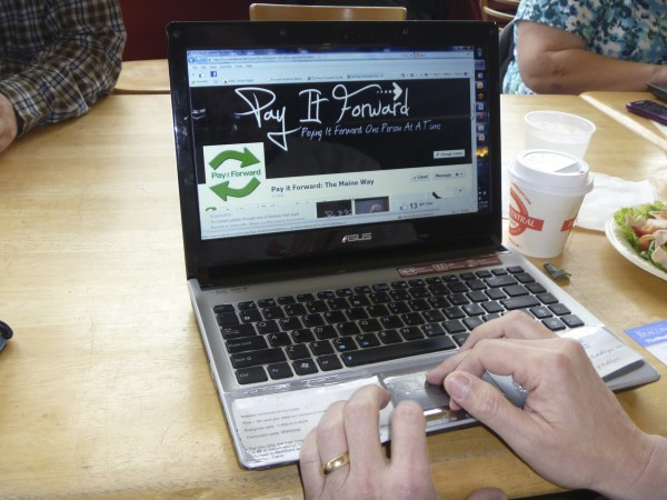 Rick Bernstein of Bangor pushes the button on his laptop to launch the Pay It Forward Facebook page on May 1 at Bagel Central in Bangor.