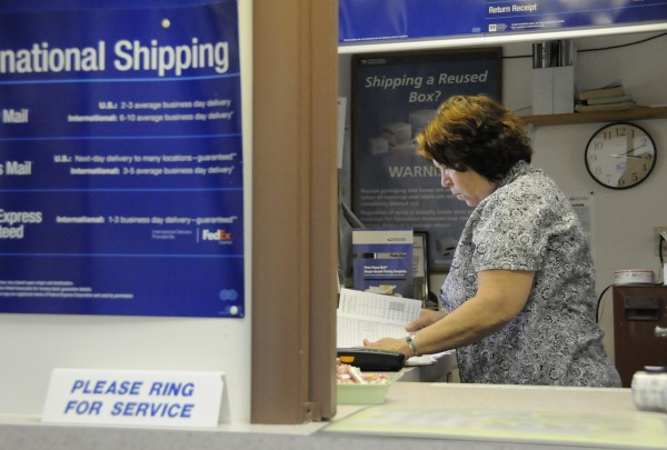 East Newport acting postmaster Barbara Henkle looks over paperwork between serving customers Tuesday afternoon, July 26, 2011.