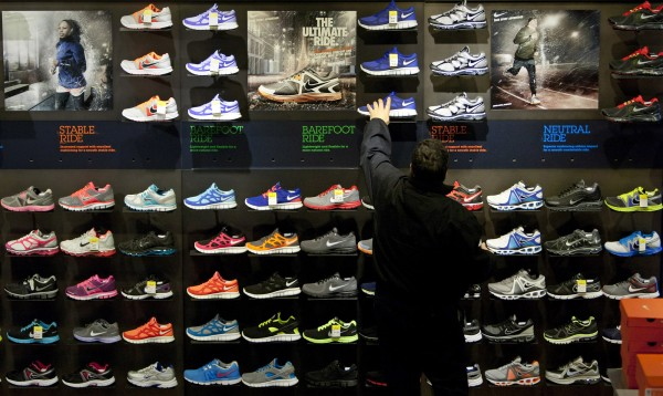 A customer shops for athletic shoes at a store in Times Square. Since the recession, Nike and Adidas have tapped into consumers' demand for more value with running shoes that are easy on not just the feet but the eyes.