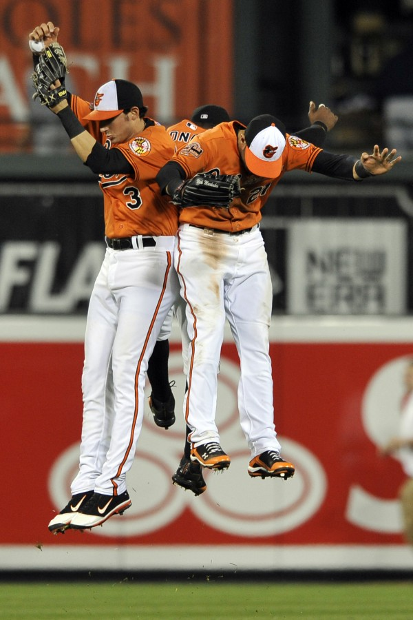 From left, Baltimore Orioles outfielders Ryan Flaherty, Adam Jones and Nick Markakis celebrate their 5-3 win against the Tampa Bay Rays in a baseball game, Saturday, May 12, 2012, in Baltimore.