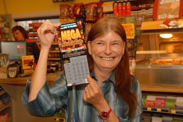 Karen Meservey of Milo is all smiles as she shows off her $20 instant game ticket that won her $500,000. She bought the ticket at LJ's Express, a gasoline and convenience store  in Milo where she is shown.