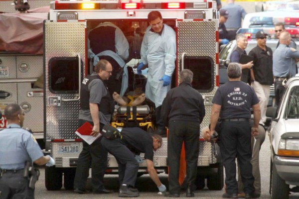 Medics work inside an ambulance on a person near the location where a homicide suspect shot himself as police closed in on him, Wednesday afternoon, May 30, 2012 in Seattle.