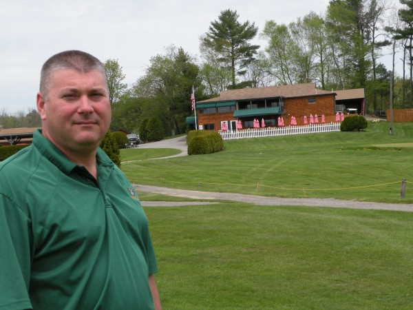 John Snyer, owner of Hermon Meadow Golf Club, with clubhouse in background.