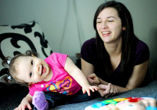 Catherine Audet of Lewiston laughs as her daughter, Haven, 1, hams it up for the camera on a recent Thursday night. Audet decided to have her child and raise her alone after an unintended pregnancy.