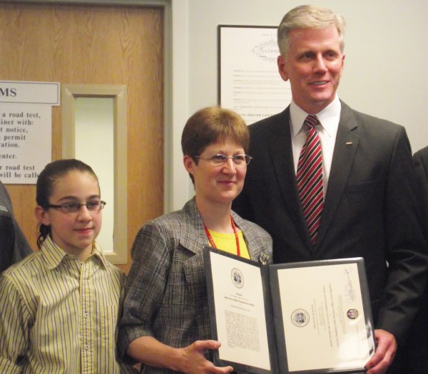 Stephanie Beaulieu (center) stands with her daughter, Sarah (left), and Secretary of State Charlie Summers at the Bureau of Motor Vehicles office in Caribou on Thursday, May 24, 2012. Beaulieu, a detective with the Maine Bureau of Motor Vehicles' Office of Investigations, was given a Secretary of State Commendation Medal in a surprise ceremony for going beyond the call of duty when she responded to a medical emergency and assisted in the delivery of a breech baby at a Fort Fairfield home last month.