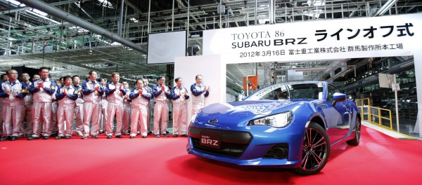 A Subaru BRZ sports coupe is driven as employees applaud at the manufacturing plant in Ota City, Japan, where the vehicle co-developed with Toyota is made. Fuji Heavy Industries, the maker of Subaru, is cranking up domestic production in spite of the strong yen.