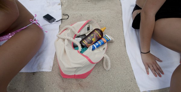 Morgan Weese (left) and Brittany Locke carry a supply of sun tanning products in their bag as they sun bathe in Miami Beach, Fla., Wednesday. Weese said she used to &quotobsessed&quot with tanning during high school, but now knows the dangers associated with tanning too much -- including skin cancer.
