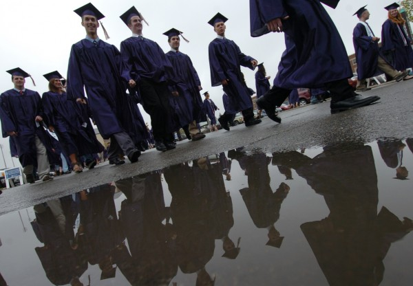Sidestepping puddles left by Saturday morning's rain, students march to Alfond Arena to receive their degrees during the morning's commencement exercises at the University of Maine in Orono.