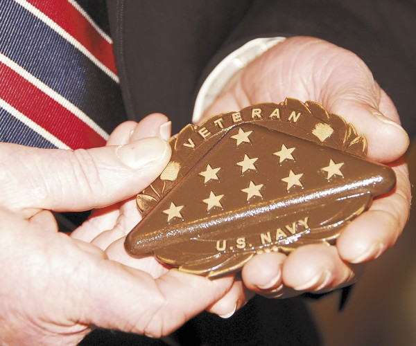 Jim Fernald of Brookings-Smith Funeral Home in Bangor holds a bronze medallion. It is affixed to a private headstone and identifies the deceased as a veteran and the military service in which the person served.