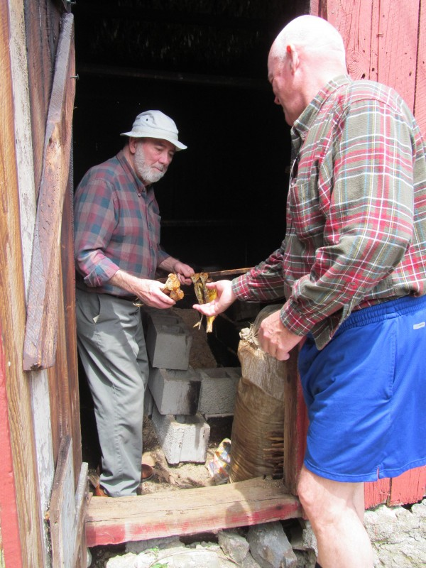 Herb Lilly Jr., who has overseen Woolwich's alewife harvest at Nequasset Creek since the 1950s, sells a few smoked fish on Sunday, May 13, 2012, to Brad Allen, a summer resident of Phippsburg, who says they are one of his favorite seafood delicacies.