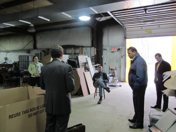 Jacob Manheimer (second from left) conducts an auction Monday, May 14, 2012 of the former Village NetMedia newspaper printing plant in Rockland. The successful bidder at this auction, and a second one held 90 minutes later in Camden, was The First bank represented by James Folsom (second from right). The only other person to submit a bid at the Rockland auction was David Bird (sitting).