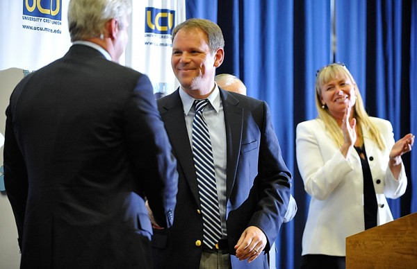 Former University of Maine women's basketball standout Emily Ellis (right) looks on as new UM women's basketball coach Richard Barron is congratulated by UM Athletic Director Steve Abbott last May. Ellis is being inducted into the Maine Sports Hall of Fame on Sunday.