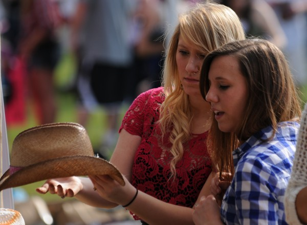 Molly Guy (left) and Nicole Turner (right), both of Brewer, inspect cowboy hats for sale during the Country Throw Down Tour on the Bangor Waterfront on Sunday, May 27, 2012.