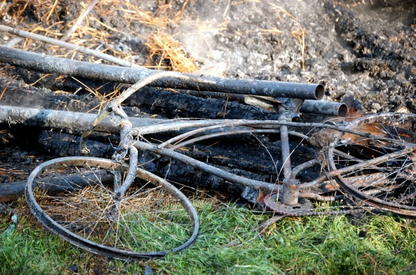 A bike near the smoldering rubble of the old wooden barn that was the centerpiece of the Darthia Farm on West Bay Road in Gouldsboro where an early Monday fire destroyed the barn and killed horses, sheep, pigs, calves and chicks that were inside.