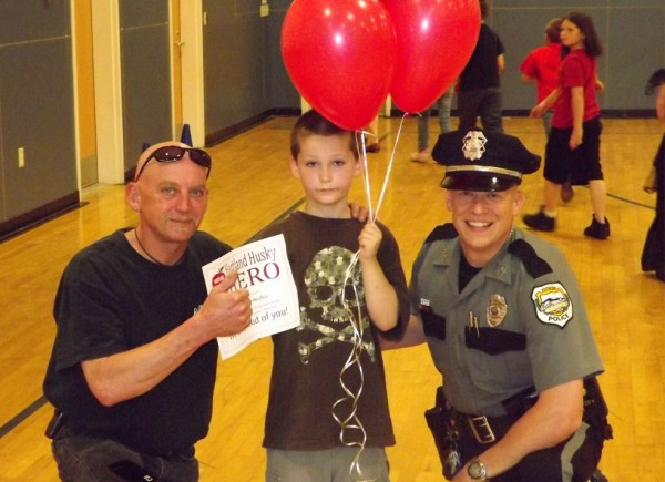 Tyler Hughes (middle) receives a hero award at Hartland Consolidated School on May 17, 2012. Hughes ran to get to attention of Darren Domonski (left) because Domonski's garage was on fire. The quick action was able to keep the garage from being leveled. Newport police Officer Chris McCrillis (right) presented the award.