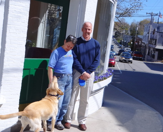 Gail and Flint Decker and their yellow Lab Annie pose outside the Bayview Street, Camden, building that now houses his New England Real Estate Company and her Antique Garden Shoppe businesses. Flint Decker helped organize the &quotBusiness is Blooming in Camden&quot event set for May 17-20.