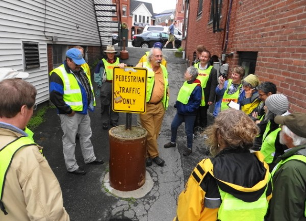 Dan Burden (leaning on sign), a consultant with expertise in making communities pedestrian friendly, pauses on a walking tour of Camden on Tuesday in an alley that leads from the town's harbor to its Main Street.
