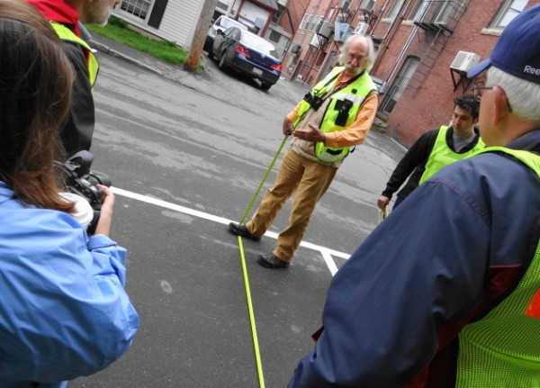 Dan Burden, an expert in making towns pedestrian friendly, measures the width of a parking space on Washington Street in Camden on Tuesday. Burden was the featured speaker in workshops in Camden and Thomaston.