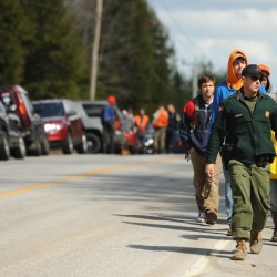 A game warden leads a group of seachers down the LaGrange Road on Tuesday, April 24, 2012, to search a wooded area for Dean Levasseur.