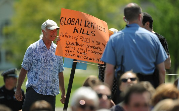 A protester stands with Jody Spear, obscured, of Brooksville, a Colby College alumnus, as she holds a sign to protest former British Prime Minister Tony Blair's presence during commencement on Sunday, May 20, 2012.