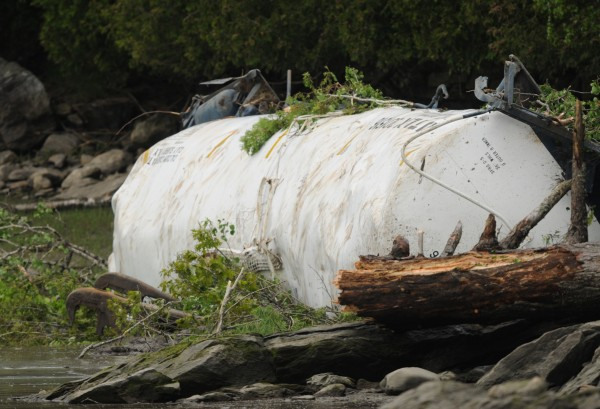 A Pan Am Railways tanker car is seen along the shoreline of the Penobscot River on  Saturday, May 26, 2012, near the Orrington-Bucksport town line after four tanker cars derailed on Friday, sending two of the tankers over an embankment and into the Penobscot River.