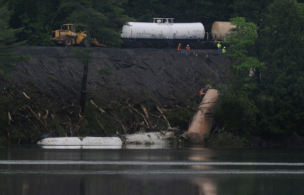 On Wednesday, May 30, 2012, crews work to remove chemicals from two train tanker cars that fell into the Penobscot River. The four cars that derailed last Friday were the first four cars after the three locomotives, which were each carrying thousands of gallons of diesel fuel and crew members. Once the chemical are removed work will begin to remove the two tanker cars from the river.