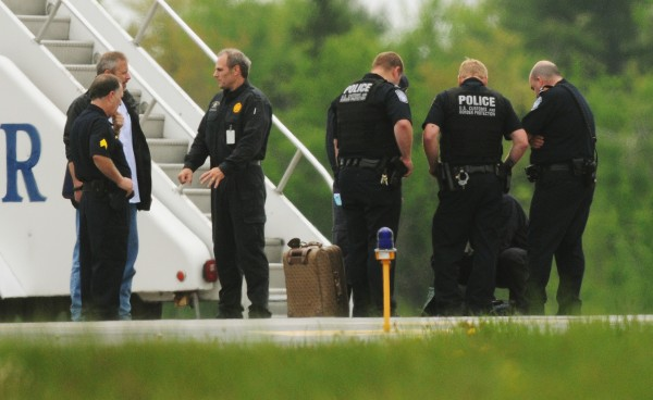 Bangor police officers gather around a suitcase that was aboard the diverted US Airways Flight 787 after a passenger claimed to have an explosive device implanted in her body on Tuesday, May 22, 2012.