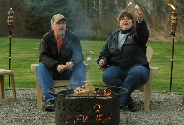 Fred and Monica Patterson toast smores over a fire in one of their custom-designed fire rings in their backyard in Brewer on Monday, April 30, 2012.