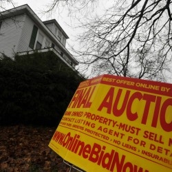 An auction sign is placed out front of a home on Bangor's west side in November 2010.