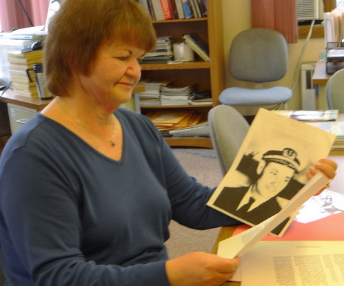 Charlene Farris, Searsport's official town historian, looks at a photo of sea captain Edwin Earle Greenlaw.